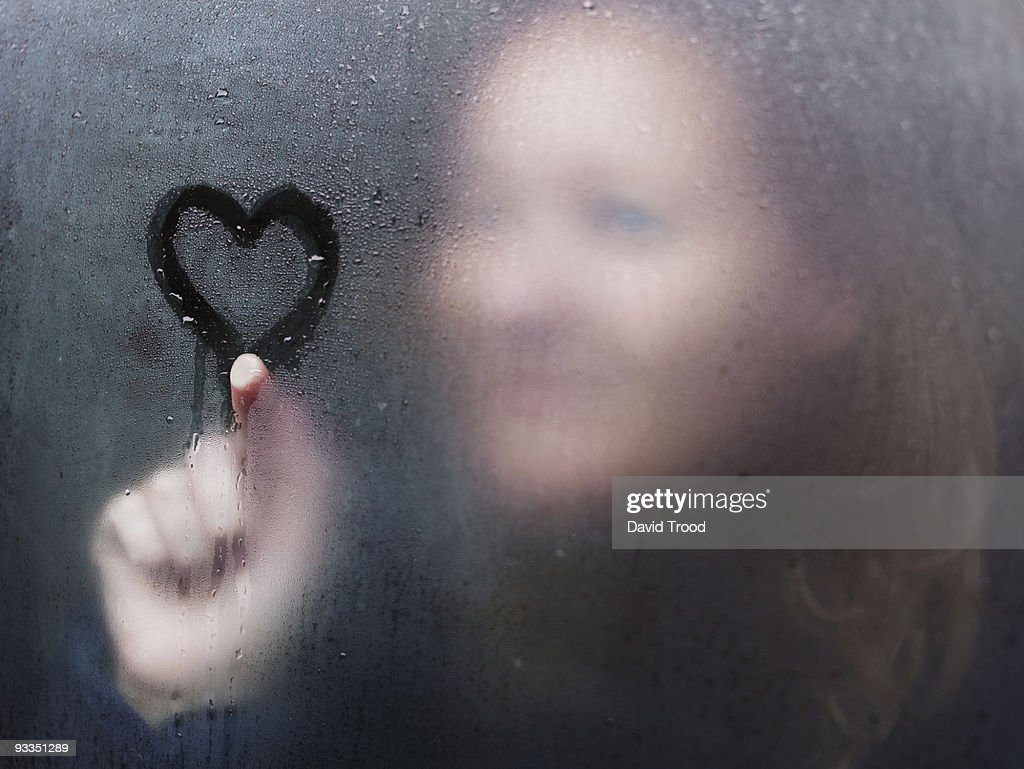 Woman drawing a heart on window on a rainy day. : Stock Photo