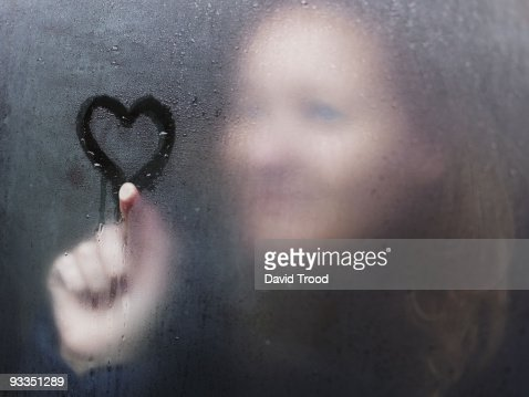 Woman drawing a heart on window on a rainy day. : ストックフォト