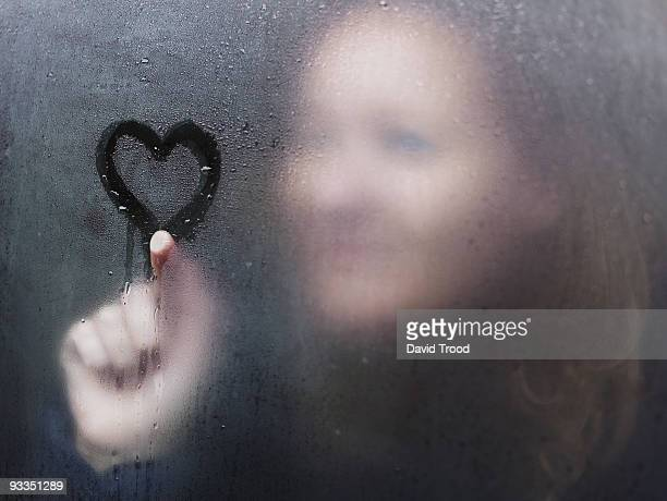 Woman drawing a heart on window on a rainy day.