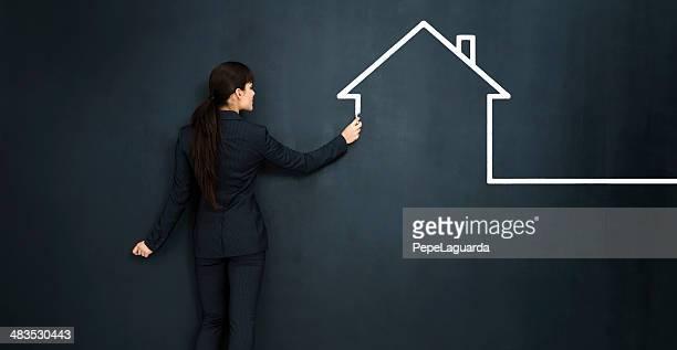 Frau zeichnen ein Haus auf große Tafel