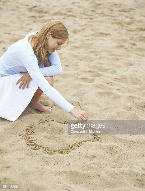 Woman drawing circle in sand, portrait