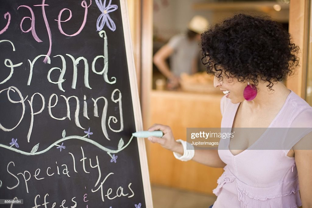 Woman drawing Grand Opening sign in cafe