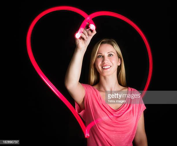 Woman drawing heart on black background