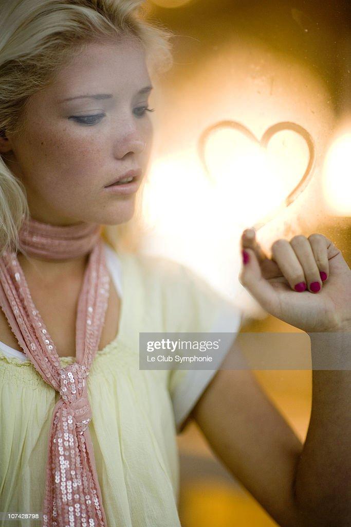 Woman drawing heart shape on glass : Stock Photo