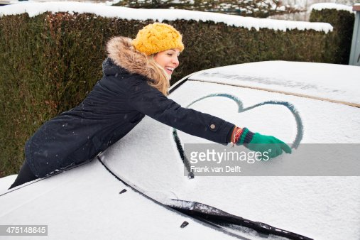 Woman drawing heart shape on snow covered windscreen