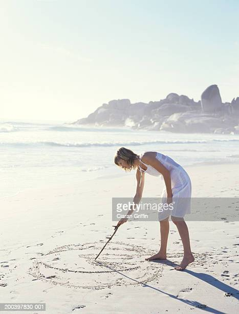 Woman drawing in sand with stick, side view