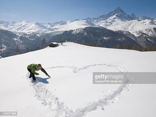 Woman draws heart in snowy mountain meadow