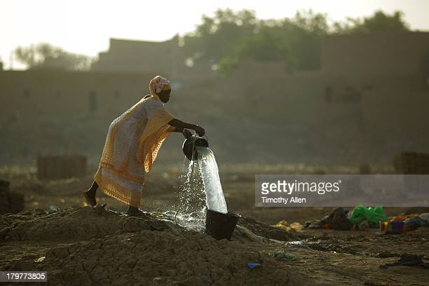 Woman draws water from a desert well, Djenne, Mali