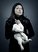 woman dress in black holding a white rabbit