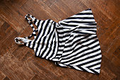 top view of woman dress with black and white stripes thrown on the wooden floor