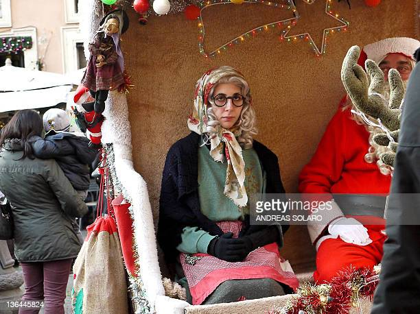 A woman dressed as a Befana a witch celebrated in Italy on the Christian festival of Epiphany on January 5 2012 sits next to Snata Claus on Piazza...