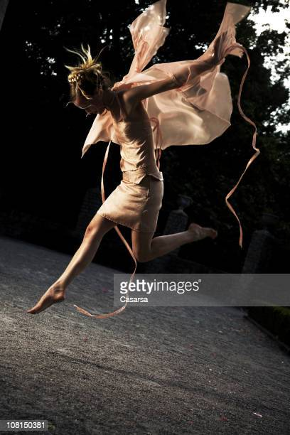 Woman Dressed as a Fairy and Jumping Outside in Courtyard