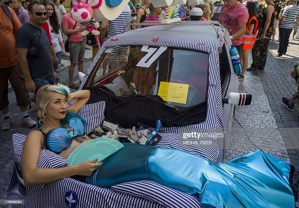 A woman dressed as a mermaid poses on a car as she takes part in the third gay pride festival in the Czech capital Prague on August 17, 2013.