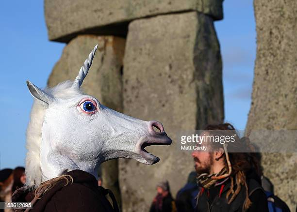 A woman dressed as a unicorn watches the sun rise as druids pagans and revellers take part in a winter solstice ceremony at Stonehenge on December 21...