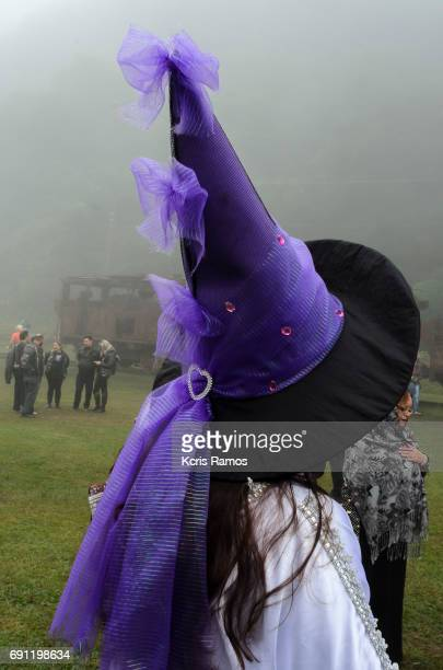 Woman dressed as a witch with a big purple hat in foggy day in the city of Paranapiacaba in São Paulo in Brazil