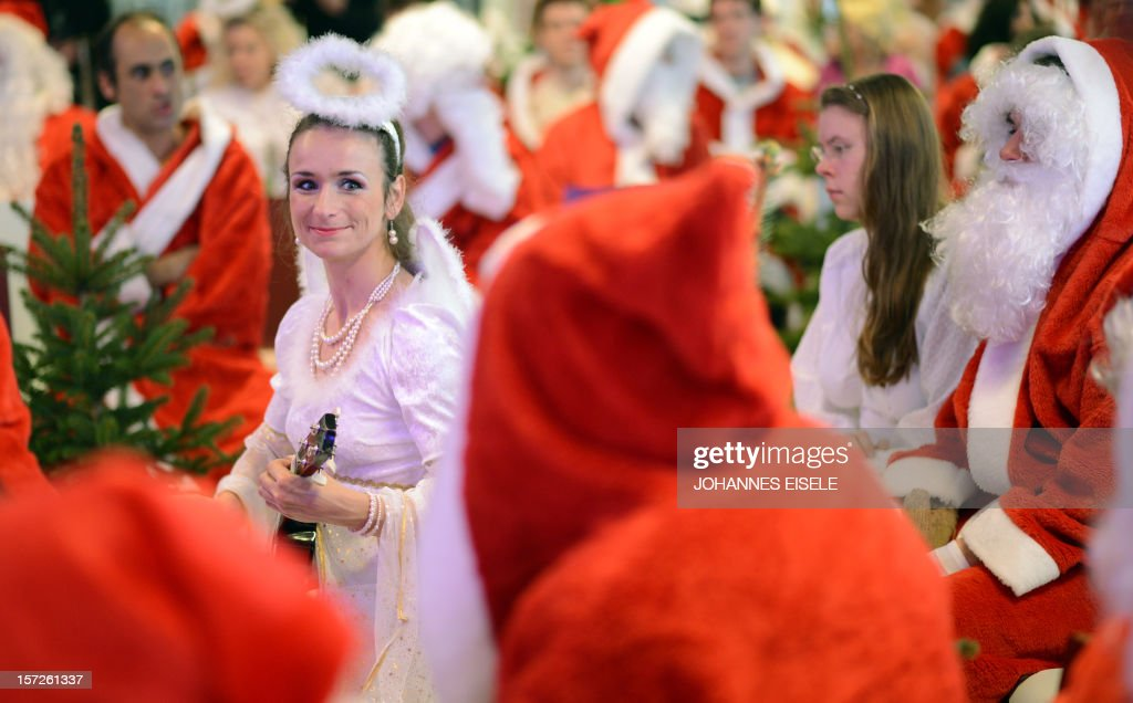 A woman dressed as an angel plays an ukulele as she attends the annual meeting of volunteer Santa Clauses and Angels on December 1, 2012 in Berlin. The event was organized by Studentenwerk Berlin, a student organization at the German capital's technical university (Technische Universitaet Berlin), that sends out its students dressed as Santas and angels every year to visit company parties in December and families on Christmas Eve. AFP PHOTO / JOHANNES EISELE