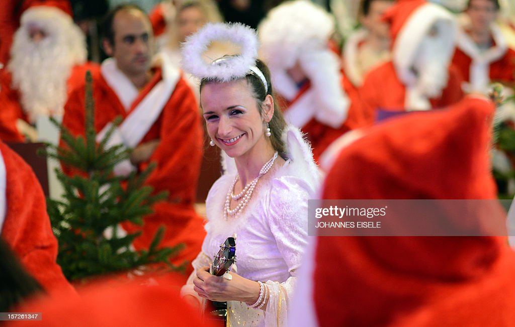 A woman dressed as an angel plays an ukulele as she attends the annual meeting of volunteer Santa Clauses and Angels on December 1, 2012 in Berlin. The event was organized by Studentenwerk Berlin, a student organization at the German capital's technical university (Technische Universitaet Berlin), that sends out its students dressed as Santas and angels every year to visit company parties in December and families on Christmas Eve.