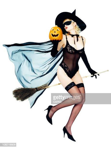 Woman Dressed as Halloween Pin-Up Witch On Her Broom