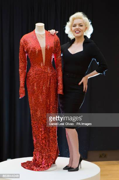 A woman dressed as Marilyn Monroe next to a red sequin gown worn by Marilyn Monroe in Gentlemen Prefer Blondes which is part of the Famous and...