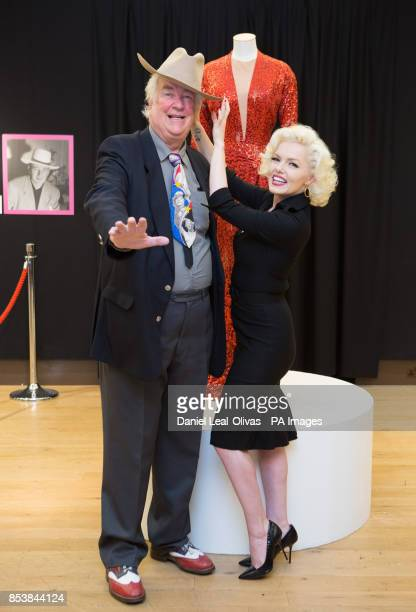 A woman dressed as Marilyn Monroe with David Gainsborough Roberts next to a red sequin gown worn by Marilyn Monroe in Gentlemen Prefer Blondes which...