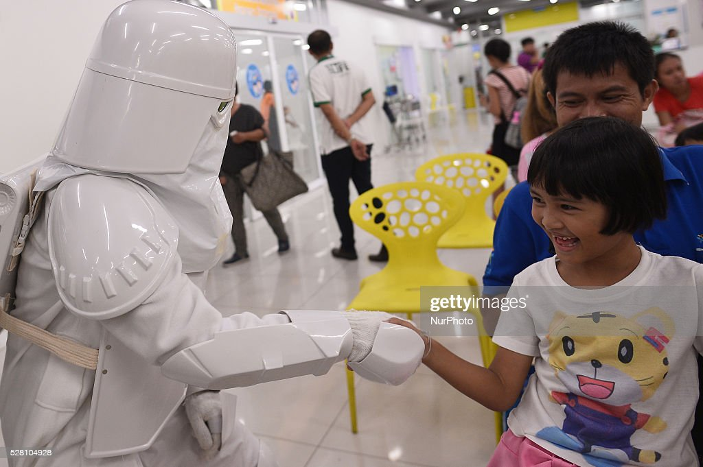 A woman dressed as the character Snowtrooper from a famous movie Star Wars plays with a girl during the Star Wars day in Bangkok, Thailand on May 4, 2016.
