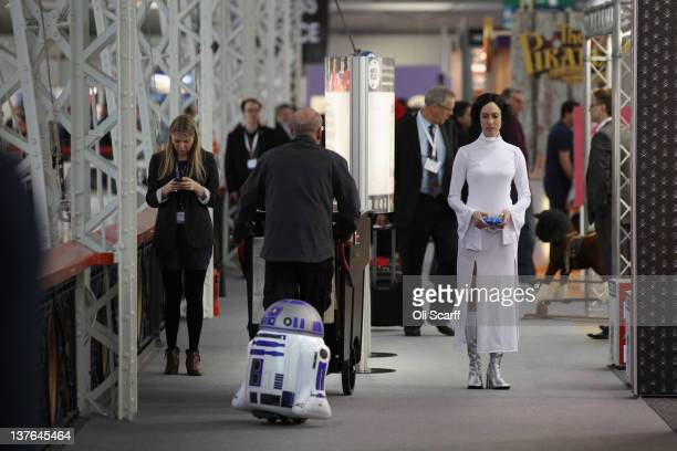 A woman dressed as the Star Wars character Princess Leia drives a radio controlled R2D2 at the 2012 London Toy Fair at Olympia Exhibition Centre on...