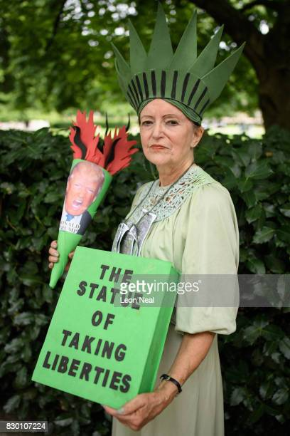 A woman dressed as 'The Statue of Taking Liberties' poses outside the US embassy during a 'Stop the War' protest on August 11 2017 in London England...