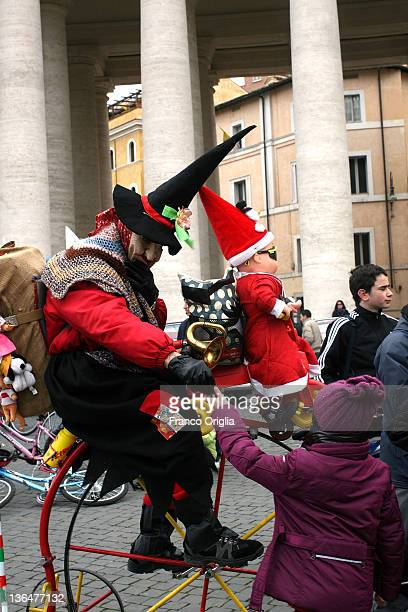 Woman dressed as the witch Befana presents sweets to children during the blessing held by Pope Benedict XVI in St Peters square after the Epiphany...