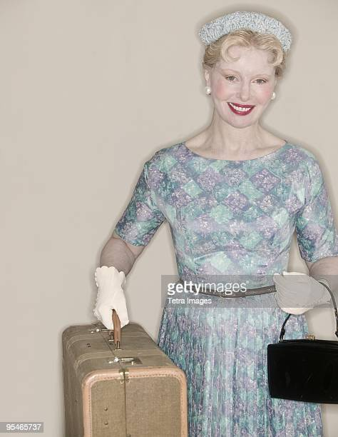 A woman dressed in 1950s clothing and carrying a suitcase