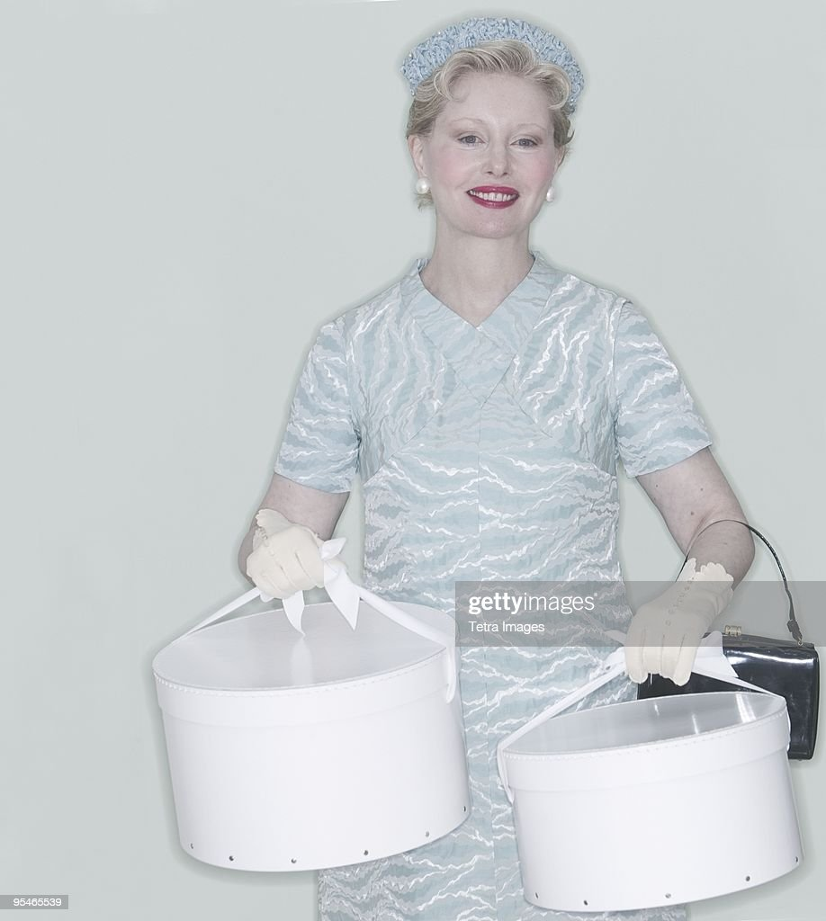 A woman dressed in 1950s clothing and carrying hatboxes