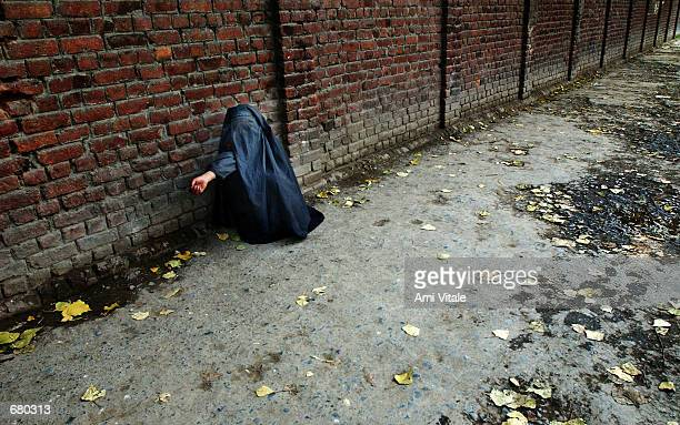 A woman dressed in a burqa begs for money November 8 2001 in Srinagar the capital of the Indian state of Kashmir Many women are afraid to go outside...