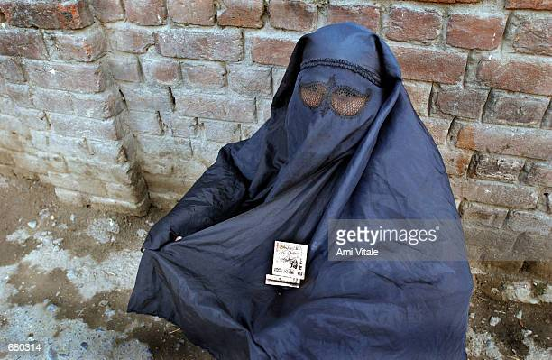 A woman dressed in a burqua begs for money November 8 2001 in Srinagar the capital of the Indian state of Kashmir Many women are afraid to go outside...