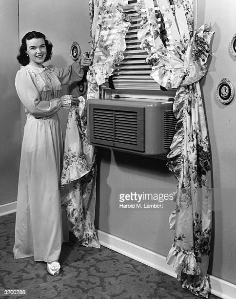 A woman dressed in a long nightgown pulls a ruffled floral print curtain back to show a modern air conditioner mounted in the window