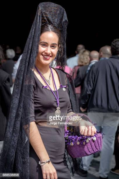 Woman dressed in a very old fashion way with the traditional 'mantilla' and 'peineta' In Seville during what is known as 'Jueves Santo' or Holy...