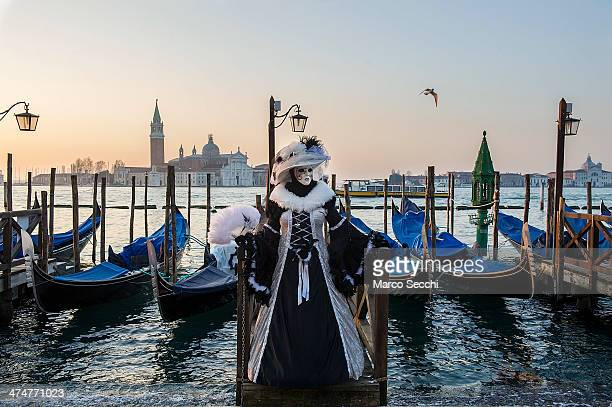 A woman dressed in Carnival Costume poses in front of gondolas in Saint Mark's Square on February 25 2014 in Venice Italy The 2014 Carnival of Venice...