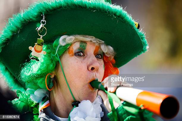 A woman dressed in colours of the Irish flag takes part in the St Patrick's Day parade through central London on March 13 2016 in London England