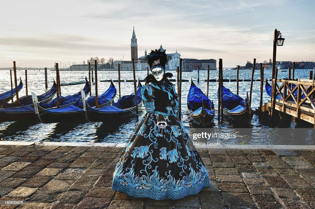 A woman dressed in costume poses in front of Gondolas in Saint Mark's Square during the Venice Carnival 2013 on February 4, 2013 in Venice, Italy. The 2013 Carnival of Venice runs from January 26 - February 12 and includes a program of gala dinners, parades, dances, masked balls and music events.