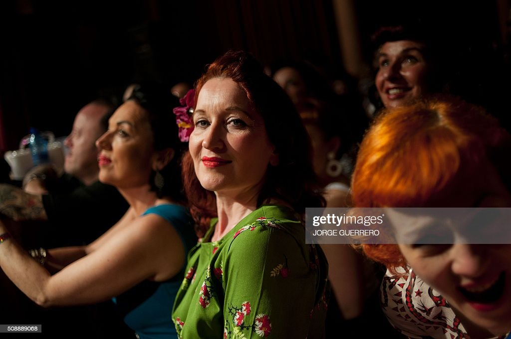 A woman dressed in fifties-style clothes looks at the camera as she attends a concert during the 22nd Rockin' Race Jamboree International Festival in Torremolinos on February 7 2016. AFP PHOTO/ JORGE GUERRERO / AFP / Jorge Guerrero