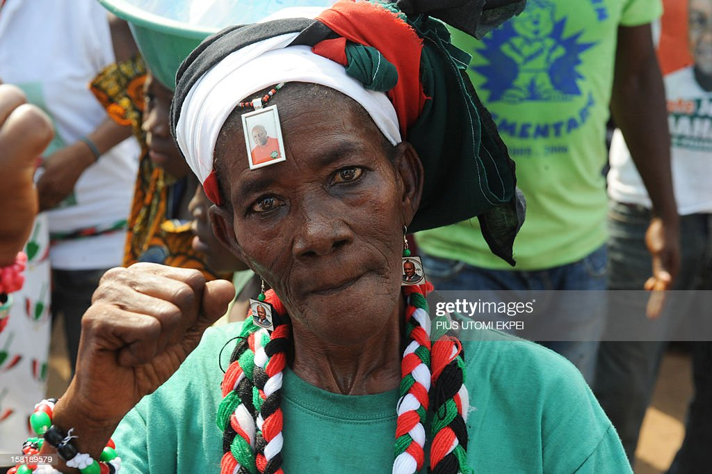 A woman dressed in Ghana's ruling National Democratic Congress party colours and wearing pictures of reelected President John Dramani Mahama on her...