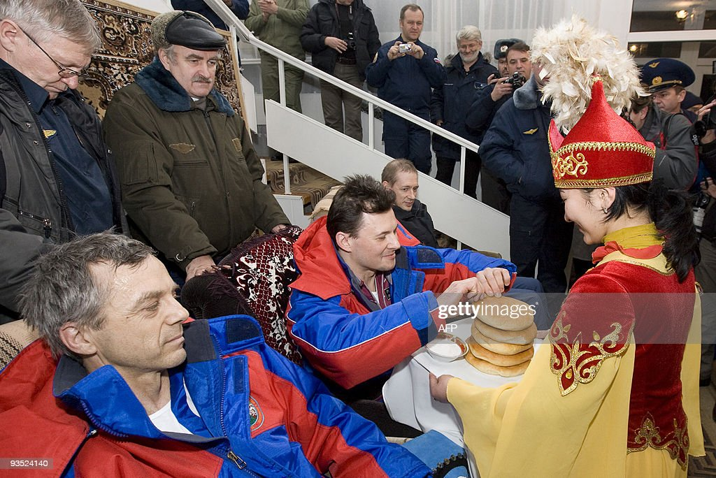A woman dressed in Kazakh national costume welcomes the International Space Station crew, European Space Agency (ESA) astronaut Frank De Winne of Belgium (R), Russian cosmonaut Roman Romanenko (C) and Canadian astronaut Robert Thirsk after arrival to Arkalyk, in northern Kazakhstan on December 1, 2009.