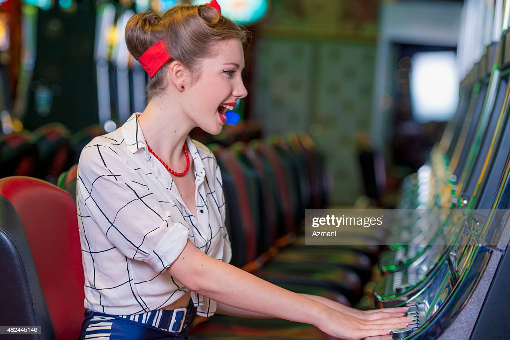 Woman Dressed in Pin-Up Style Playing on a Slot Machine : Stock Photo