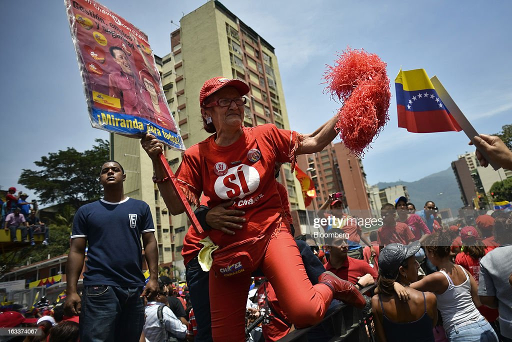 A woman dressed in red climbs over a fence while holding a sign and pom poms during the funeral for Venezuelan President Hugo Chavez in Caracas, Venezuela, on Friday, March 8, 2013. Allies of Venezuela's Hugo Chavez paid their final respects to the firebrand socialist leader at a state funeral that marked the emotional high point of a week of tributes preceding a snap election to choose his successor. Photographer: Meridith Kohut/Bloomberg via Getty Images