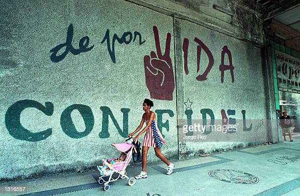 A woman dressed in the colors of the United States flag pushes her baby as they walk past a wall that reads 'A Lifetime with Fidel' June 11 2001 in...