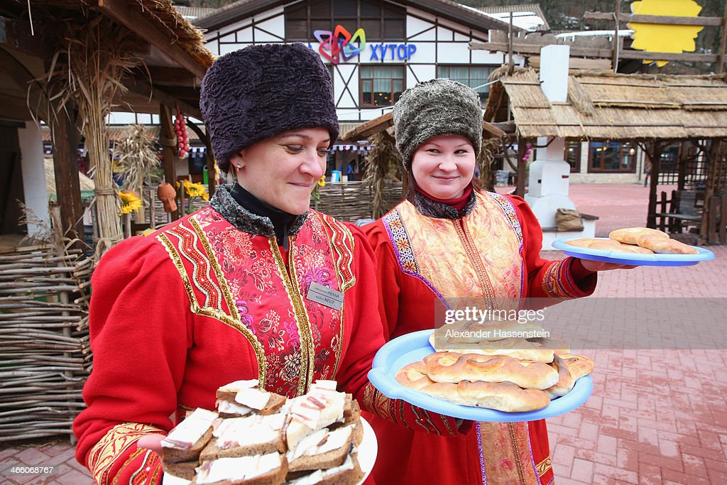 Woman dressed in their traditional Russian outfit serve local food at the center of the Rosa Khutor Mountain Cluster village ahead of the Sochi 2014 Winter Olympics on January 31, 2014 in Rosa Khutor, Sochi, Russia.