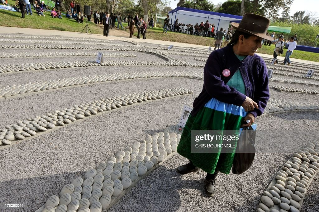A woman dressed in typical Andean attire walks around a symbolic graveyard of stones reading names of victims of the war against terrorist groups as The Shinning Path and the Tupac Amarus during the 80's and 90's, in Lima on August 28, 2013. Relatives of victims commemorate the 10th anniversary of the release of the report of the Commission of Truth and Reconciliation of Peru, which concluded that there were 69.000 people killed or missing during the 80's and 90's.