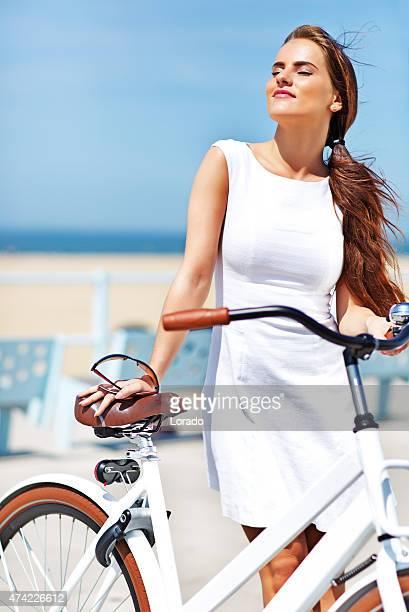 woman dressed in white  holding white bike enjoying the sun