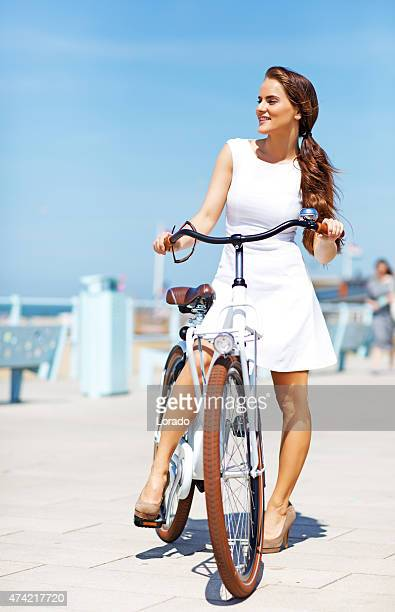woman dressed in white  holding white bike walking near North sea