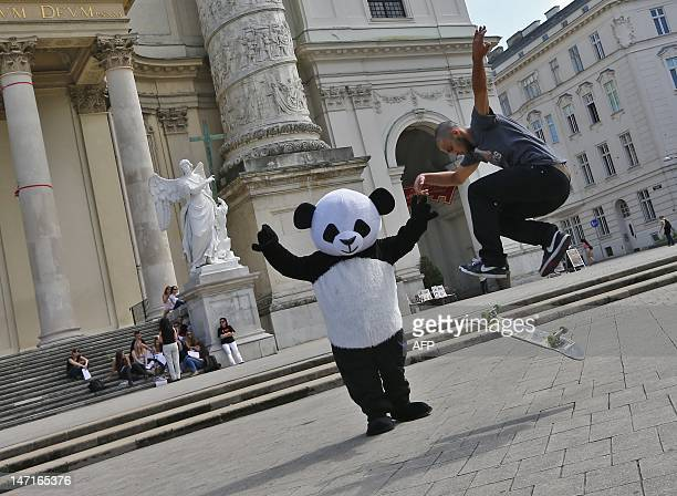 A woman dressed up as a panda gestures as a skateboarder performs a ollie flip in front of the Karlskirche in Vienna on June 26 2012 AFP PHOTO /...
