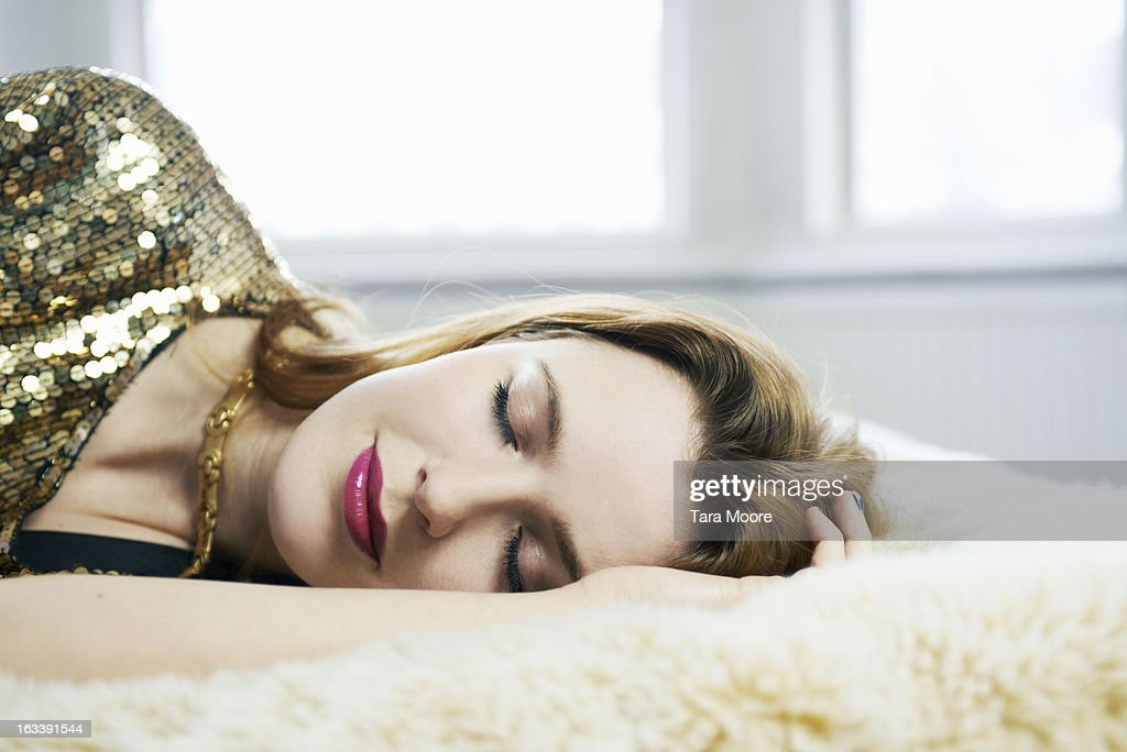 woman dressed up asleep on bed