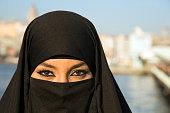 Woman dressed with black headscarf, chador on istanbul street, turkey